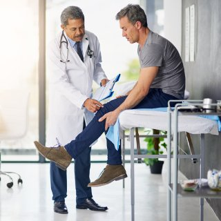 man chatting to a doctor getting examined